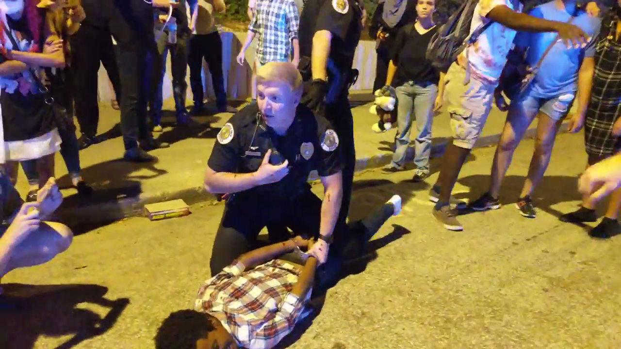 A Georgia Tech police officer handcuffs a protester, who is lying facedown on the ground, at a protest after the shooting death of Scout Schultz.