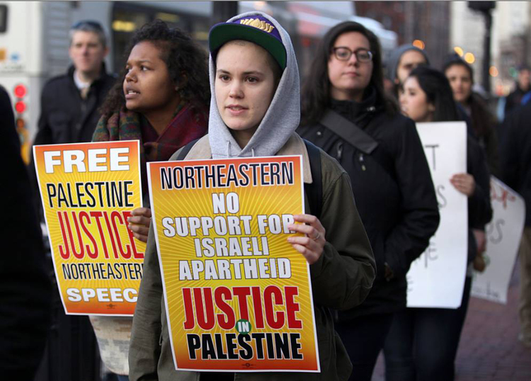 "Protesters at Northeastern University holding signs reading ""Free Palestine,"" ""No support for Israeli apartheid."""