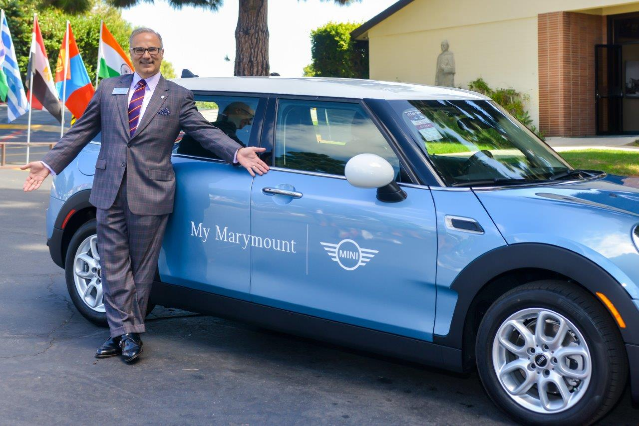 "Former Marymount California president Lucas Lamadrid poses with a Mini Cooper automobile as part of the ""My Marymount Mini"" program announced in 2016."