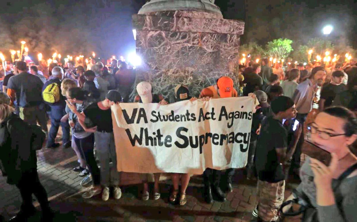 "Counterprotesters against a white nationalist gathering hold a sign saying ""VA Students Act Against White Supremacy."" The counterprotesters are at the foot of a statue of Thomas Jefferson and are surrounded by torch-bearing white nationalists."