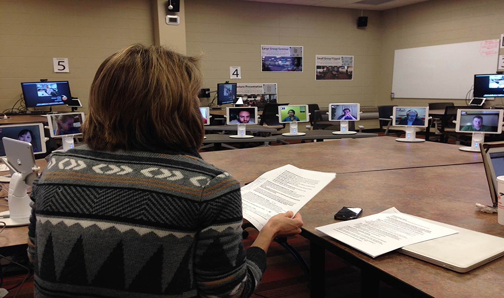 Image of Christine Greenhow in her classroom, surrounded by iPads enabling students to participate remotely.