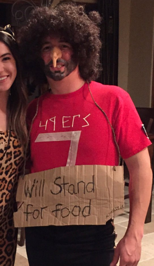 Photo of a white student in costume as Colin Kaepernick, wearing a bushy wig, fake nose and 49ers T-shirt.