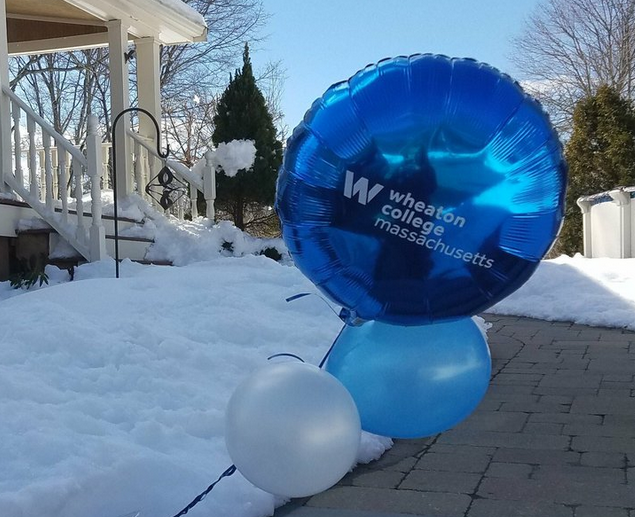 Image of a front porch surrounded by snow and blue Wheaton College Massachusetts balloons.