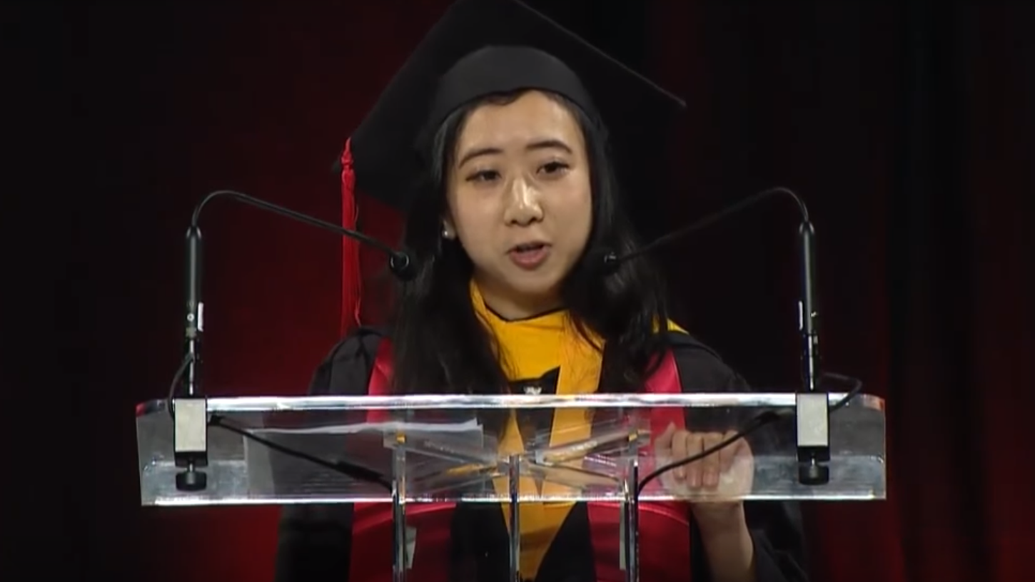 Shuping Yang, wearing academic regalia, speaks at the University of Maryland, College Park.