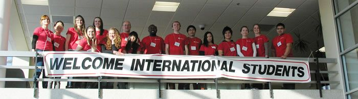 "College students with a banner saying ""Welcome International Students."""