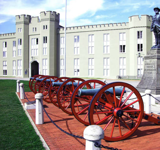 Picture of Stonewall Jackson statue at Virginia Military Institute, behind a line of red cannons.