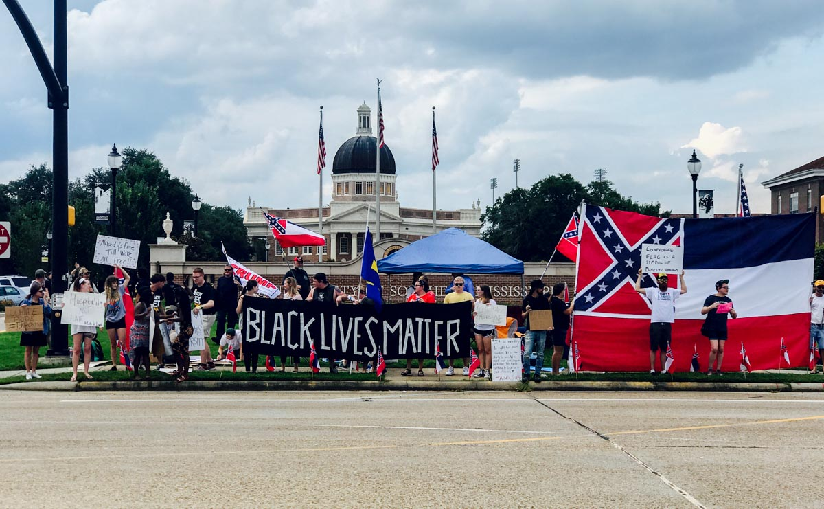 "Image of Aug. 13 protest shows a sign with the words ""Black Lives Matter,"" as well as Confederate and Mississippi flags."
