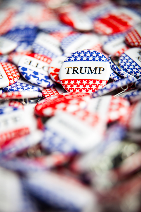 "Red, white and blue buttons, some saying ""Vote,"" some saying ""Trump."""
