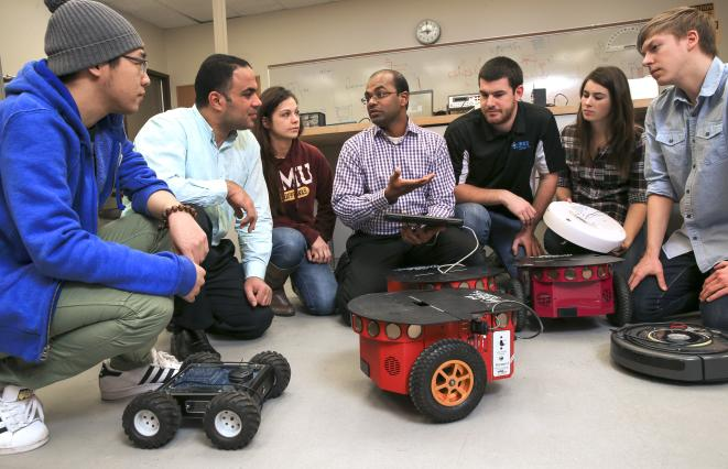 Kumar Yelamarthi, professor of electrical engineering at Central Michigan University, looks at circuit projects with his students