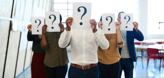 Stock image of people holding up pieces of paper with question marks in front of their faces.