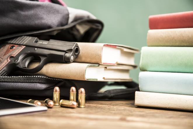 Stock image of handgun next to bullets and a stack of books.