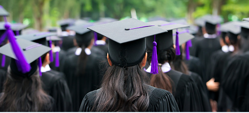 Image of graduates in mortarboards with purple tassels.