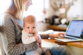 Stock image of a woman holding a baby on her lap while typing on a computer.